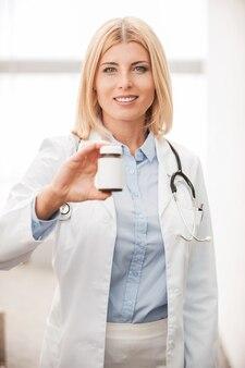 Heilende medikamente. selbstbewusste ärztin in weißer uniform, die einen behälter mit medikamenten hält und lächelt