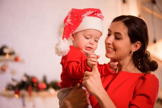 Heiligabend. familie mutter und baby in santa hatplay spiel zu hause in der nähe des kamins