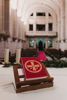 Heilige bibel auf tabelle während einer hochzeitszeremoniemasse. religion-konzept. ornamente der katholischen eucharistie zur feier der eucharistie