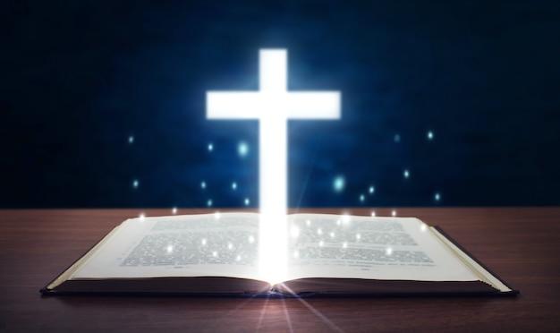 Heilige bibel mit leuchtendem kreuz.