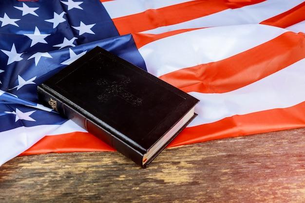 Heilige bibel und die flagge der vereinigten staaten im hintergrund.