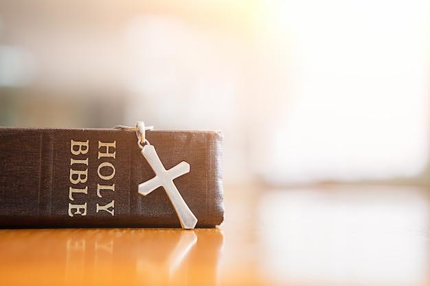 Heilige bibel und kreuz auf dem tisch.