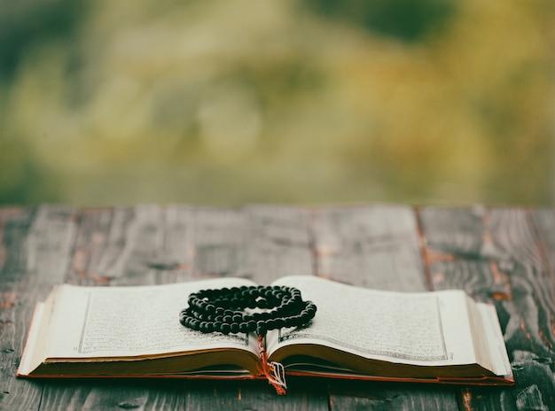 Heilige perlen aus holz, die ein geöffnetes koran-religionslehrbuch mit verschwommenem grünem hintergrund kopieren.