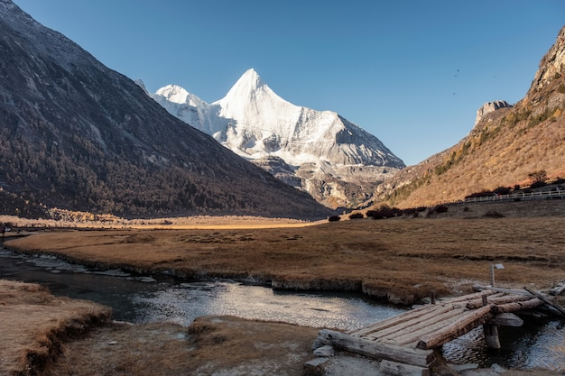 Heilige schneegebirgs-yangmaiyong-reflexion über fluss im herbsttal auf hochebene