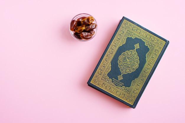 Heiliger al quran mit geschriebener arabischer kalligraphie, die al quran bedeutet und auf einem hellrosa raum datiert. platz für text. ramadan kareem. russland - 5. mai 2020