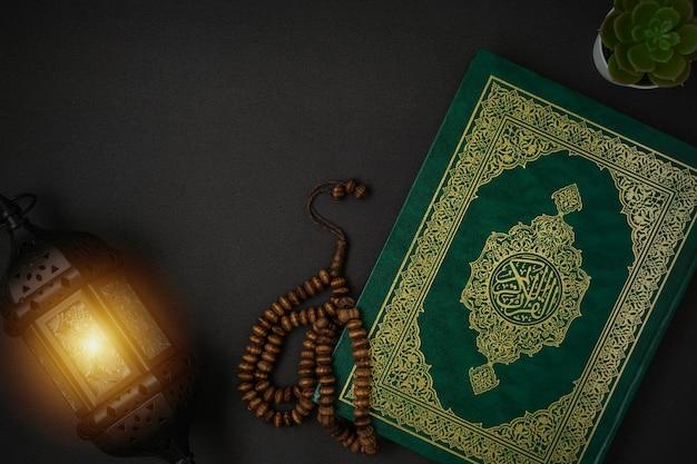 Heiliger al quran mit geschriebener arabischer kalligraphiebedeutung von al quran und rosenkranzperlen auf schwarzem hintergrund mit einem kopienraum