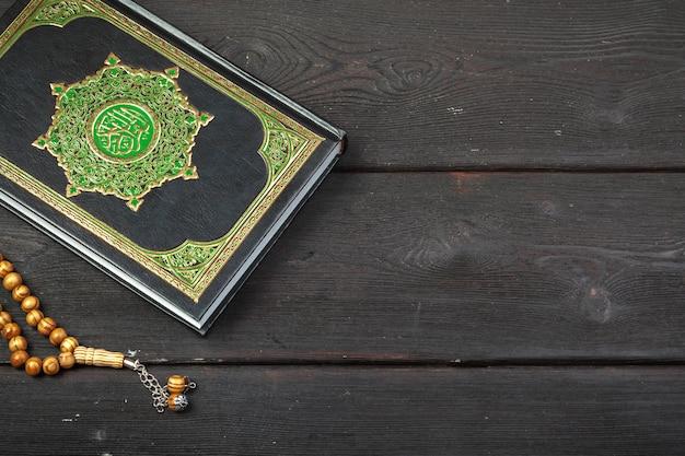 Heiliger koran mit perlen über holzoberfläche