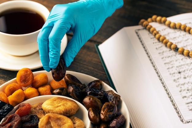 Heiliger monat ramadan, nahaufnahme hände in medizinischen handschuhen nehmen daten, iftar-konzept, koran-buch, hölzerner rosenkranz, tasse tee, quarantäne