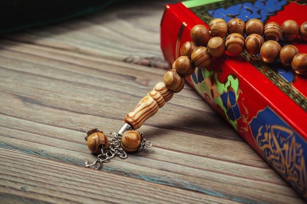 Heiliger quran mit perlen über holzoberflächeabschluß oben
