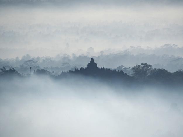 Heiliger tempel von borobudur in einem schönen nebligen sonnenaufgang vom setumbu hill aus gesehen