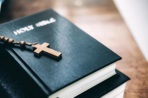 Heiliges bibble mit christlichem kreuz auf tabelle.
