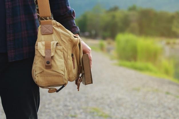 Heiliges bibelmännchen, das eine tasche trägt und die bibel mit naturhintergrundspiritualität und religion hält