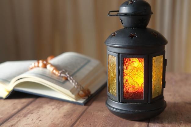 Heiliges buch koran, rosenkranz und lederlampe auf dem tisch