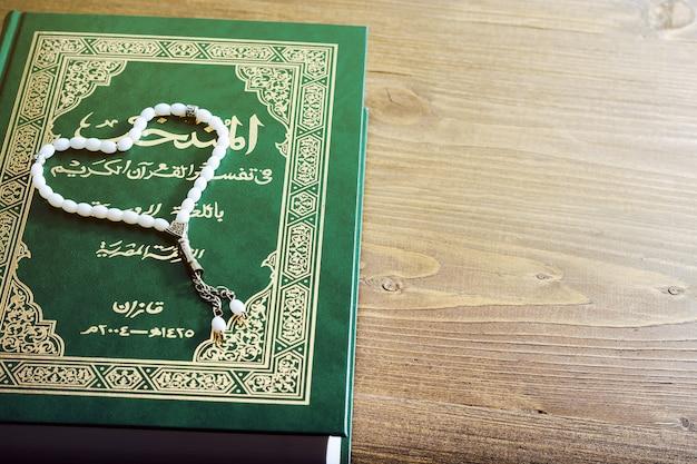 Heiliges quran-buch mit rosenkranz. gebetskonzept. getönt