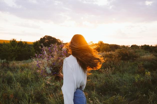 Heilkraft der natur, vorteile der ökotherapie, naturbeeinflussung des wohlbefindens. glückliches junges mädchen, das wildblumenstrauß hält, sich entspannt und das leben genießt