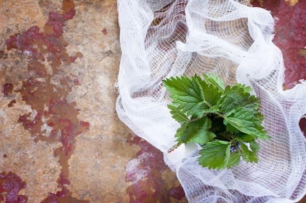 Heilpflanze frische brennnesselblätter, selektiver fokus. frisches brennnesselblatt auf dem küchentisch ein rustikaler hintergrund. draufsicht, kopierraum.