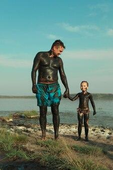 Heilschlamm für den körper. schlammbäder am see. ein mann und ein kind werden mit lehm bestrichen. familie im resort