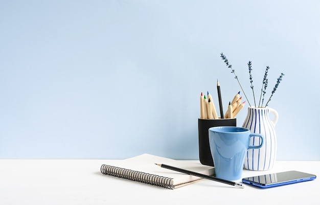 Heim- und büroschreibtisch mit notizblock, telefon, bleistiften, kaffee, auf einem weißen tisch über hellblauer wand. mockup mit kopienraum