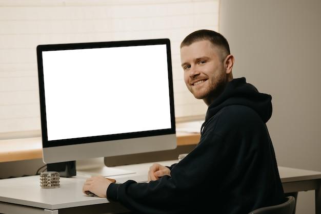 Heimarbeit. ein geschäftsmann arbeitet remote mit einem all-in-one-computer. ein lächelnder kerl mit bart, der von zu hause aus arbeitet.