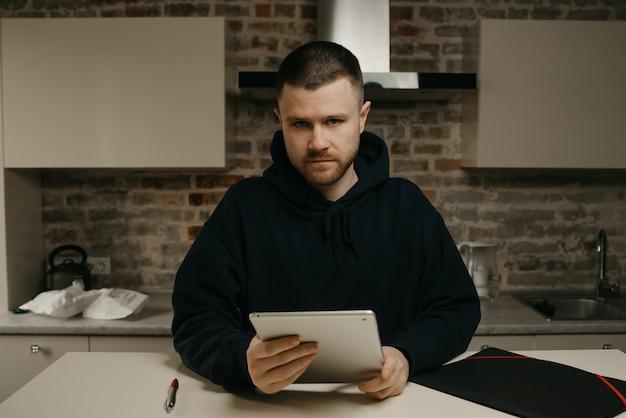 Heimarbeit. ein mann arbeitet aus der ferne und hält sein tablet. ein geschäftsmann mit bart, der direkt in seiner küche arbeitet.
