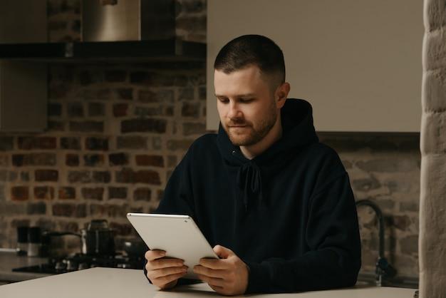 Heimarbeit. ein mann, der aus der ferne an seinem tablet arbeitet. ein geschäftsmann mit bart, der zu hause arbeitet.