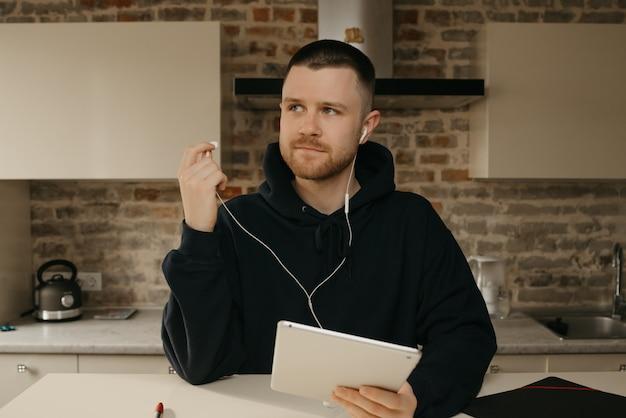 Heimarbeit. ein mann mit bart, der aus der ferne an seinem tablet arbeitet. ein geschäftsmann unterbrach ein gespräch mit seinen kollegen über ein unternehmen durch eine videokonferenz.