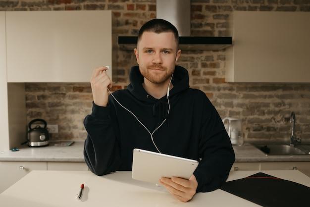 Heimarbeit. ein mann mit bart, der aus der ferne an seinem tablet arbeitet. ein geschäftsmann unterbrach einen anruf mit seinen kollegen über ein geschäft durch eine videokonferenz.