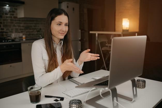 Heimarbeit. eine brünette frau mit kopfhörern, die aus der ferne online an ihrem laptop arbeitet. ein mädchen, das aktiv mit seinen kollegen über einen videoanruf an ihrem gemütlichen arbeitsplatz zu hause über geschäfte spricht.