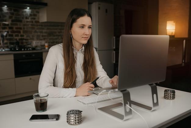 Heimarbeit. eine kaukasische brünette frau mit kopfhörern, die entfernt online auf ihrem laptop arbeiten. ein mädchen in einem weißen hemd, das einen videoanruf zu ihren geschäftspartnern an ihrem gemütlichen heimarbeitsplatz macht.