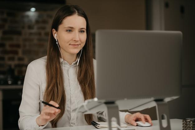 Heimarbeit. eine kaukasische brünette frau mit kopfhörern, die fern an ihrem laptop arbeiten. eine geschäftsfrau in einem weißen hemd, die geschäft an ihrem hauptarbeitsplatz macht.