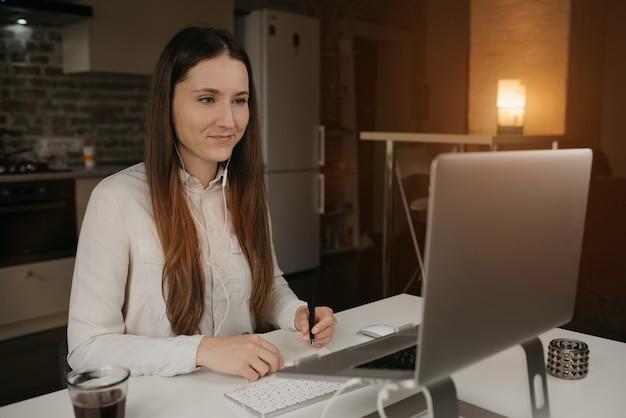 Heimarbeit. eine kaukasische frau mit kopfhörern, die fern an ihrem laptop arbeiten. ein brünettes mädchen in einem weißen hemd, das notizen während einer online-geschäftsbesprechung an ihrem gemütlichen heimarbeitsplatz macht.