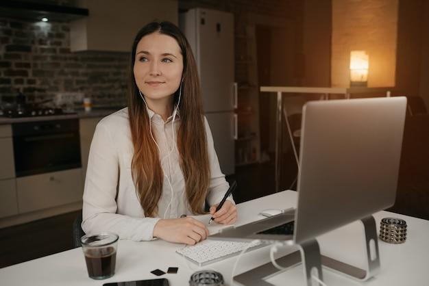 Heimarbeit. eine kaukasische frau mit kopfhörern, die fern an ihrem laptop arbeiten. ein glückliches brünettes mädchen mit einem lächeln, das notizen während einer online-geschäftsbesprechung an ihrem gemütlichen heimarbeitsplatz macht.