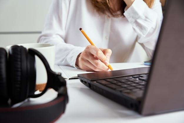 Heimarbeit. frau macht notizen im notizbuch und benutzt laptop zum lernen. fernunterricht und e-learning-konzept