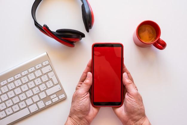 Heimarbeiter machen eine pause mit kaffeetasse mit telefon mit rotem bildschirm und roten kopfhörern