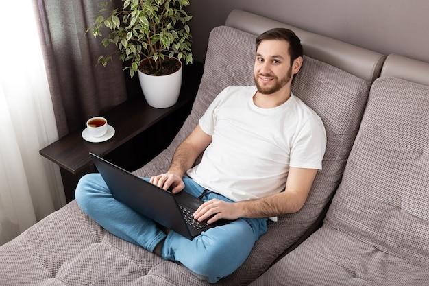 Heimarbeitsplatz. mann freiberuflich im gesicht chirurgische maske arbeiten von zu hause aus mit laptop. gemütliches arbeitszimmer auf dem sofa.