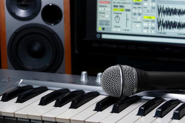 Heimaufnahmestudio. bildschirm, tastatur, lautsprecher und mikrofon.
