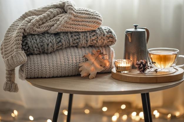 Heimherbstkomposition mit tee und strickpullovern im inneren des raumes, auf unscharfem hintergrund mit girlande.
