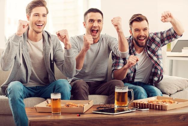 Heimische fans. drei glückliche junge männer, die fußballspiele gucken und die arme gehoben halten, während sie auf dem sofa sitzen