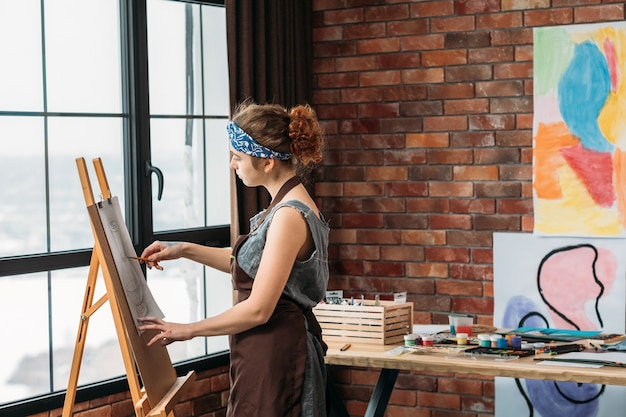 Heimkunststudio. seitenansicht der jungen malerin, die auf staffelei zeichnet. fenster, backsteinmauer mit abstrakten kunstwerken