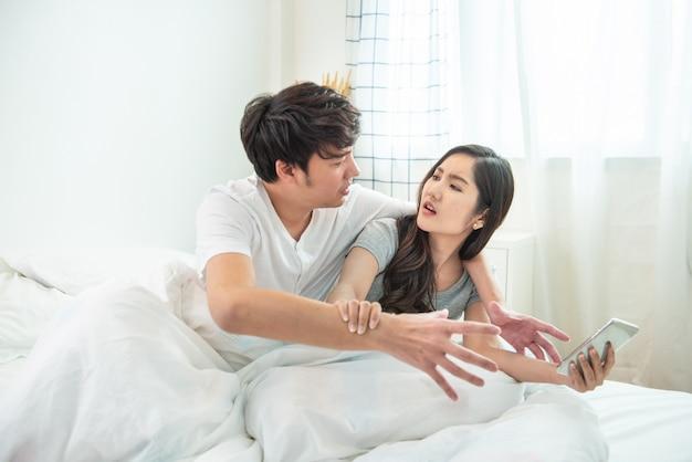Heimlich konversation über telefon hören oder soziale beiträge, nachrichten gucken. asiatischer junger mann und frau streiten sich auf intelligentem handy mit argumentationsbeziehungskonzept