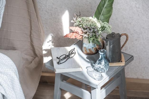 Heimstuhl mit einem schönen blumentopf und dekorationsgegenständen