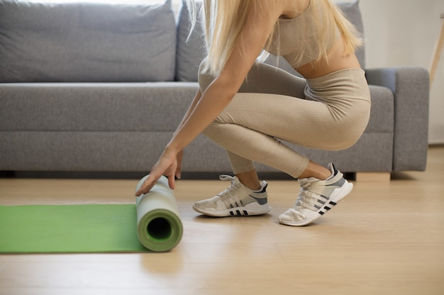 Heimtraining. frau rollende yogamatte nach dem training zu hause.
