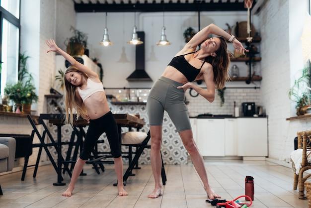 Heimtraining. mutter und tochter trainieren zusammen, indem sie seitenbiegeübungen machen.