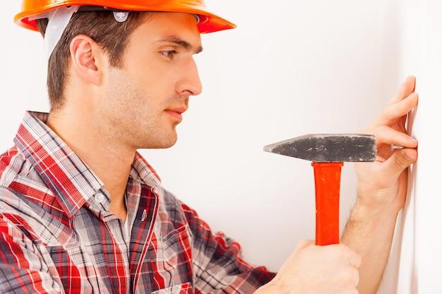 Heimwerken. seitenansicht eines hübschen jungen handwerkers in bauarbeiterhelm, der einen nagel hämmert, während er in der nähe der wand steht