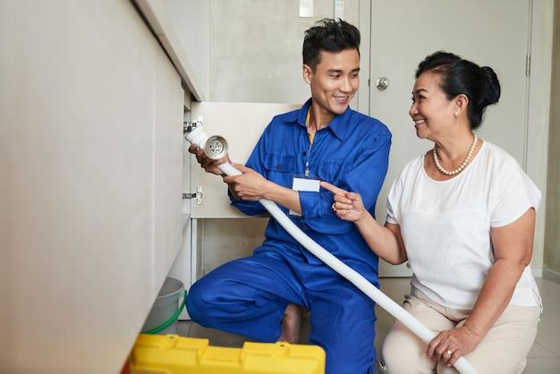 Heimwerker, der älterer frau in der küche hilft
