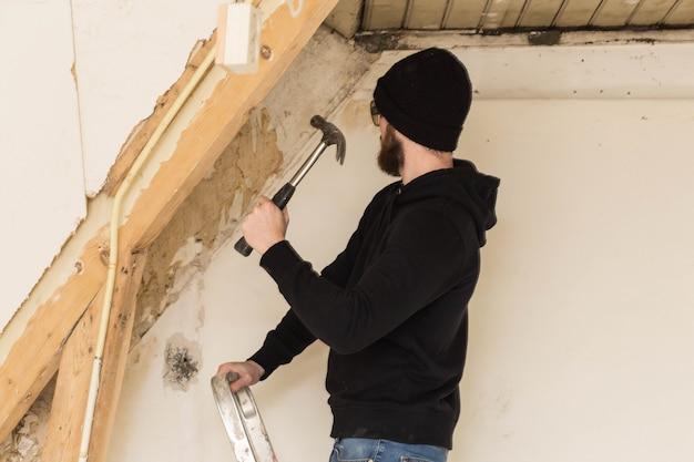 Heimwerker, der auf einer leiter steht und ein haus, unter verwendung der werkzeuge wie ein hammer erneuert