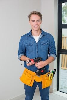 Heimwerker, der einen bohrer mit toolbelt um taille hält