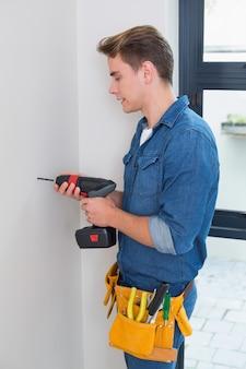 Heimwerker, der einen bohrgerät mit toolbelt um taille verwendet