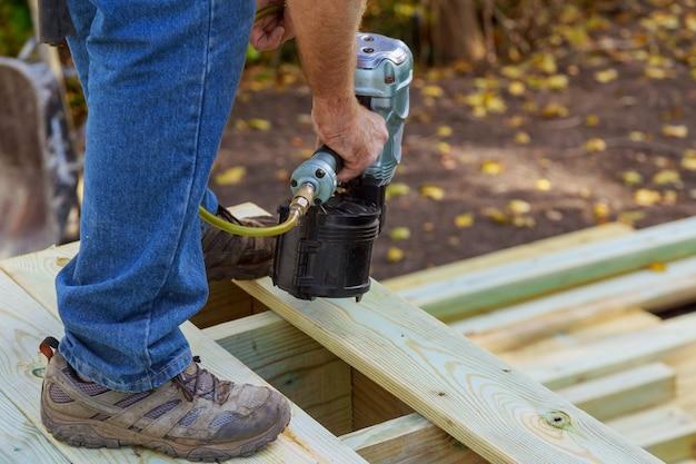 Heimwerker, der hölzernen bodenbelag in patio, arbeitend unter verwendung der nagelpistole installiert, um zu nageln