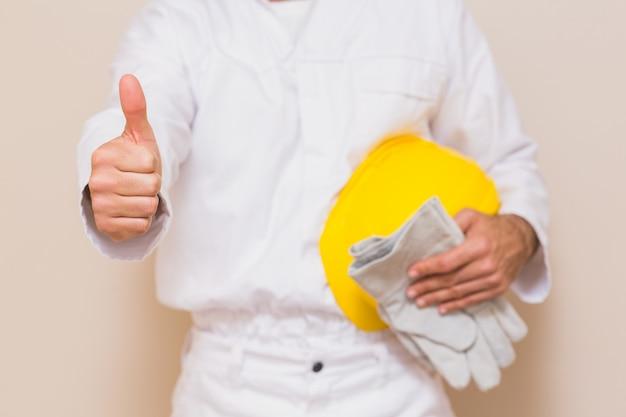 Heimwerker, der seinen gelben sturzhelm sich zeigt daumen hält